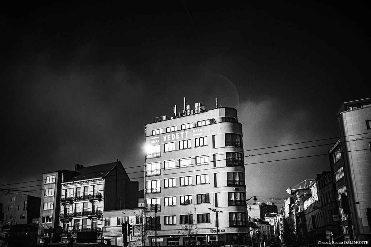 Frontière entre Bruxelles-Ville et Molenbeek, la Porte de Flandre s'ouvre au regard dans un éclat de lumière pour nous montrer un immeuble dominé par l'enseigne de la bière Vedett qui s'intègre au style vintage de la gentrification.© 2014 Bruno D'ALIMONTE
