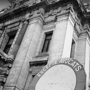 Photographie en noir et blanc du palais de justice de Bruxelles avec comme avant-plan un panneau d