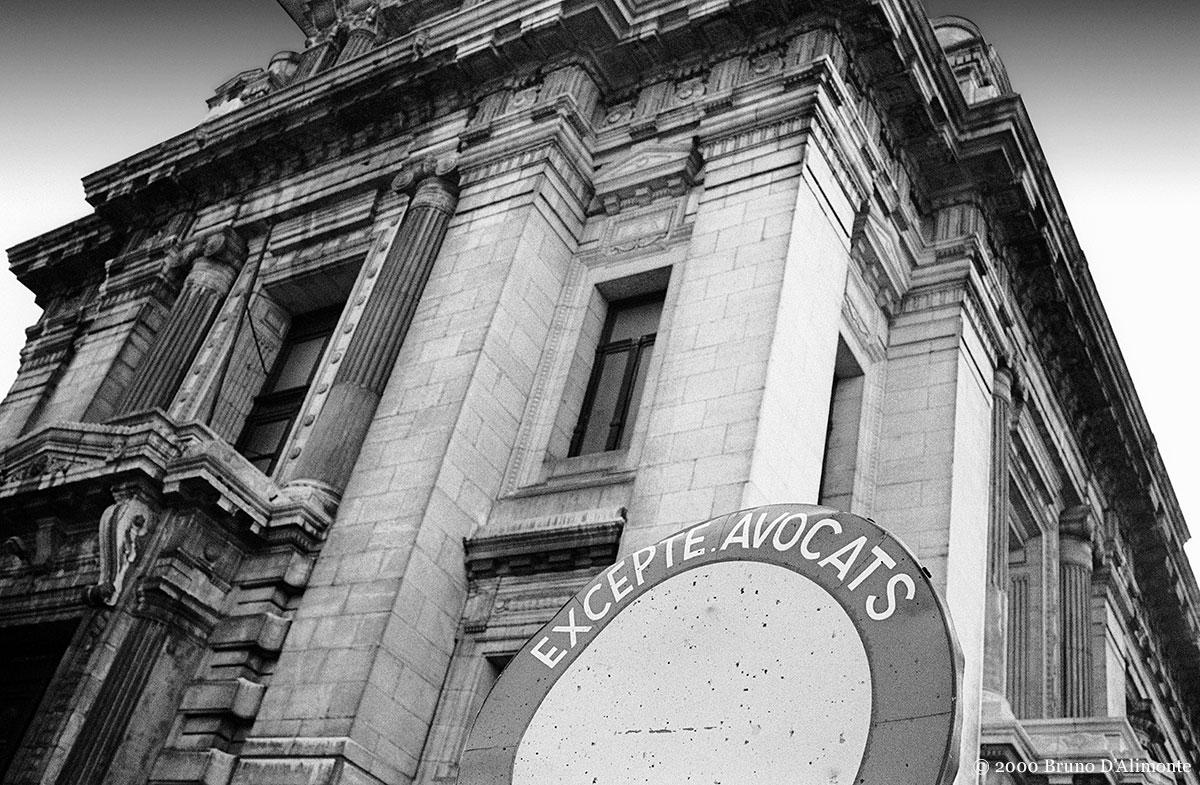 Photographie en noir et blanc du palais de justice de Bruxelles avec comme avant-plan un panneau d'interdiction de circuler à l'exception des avocats.© 2000 Bruno D'Alimonte