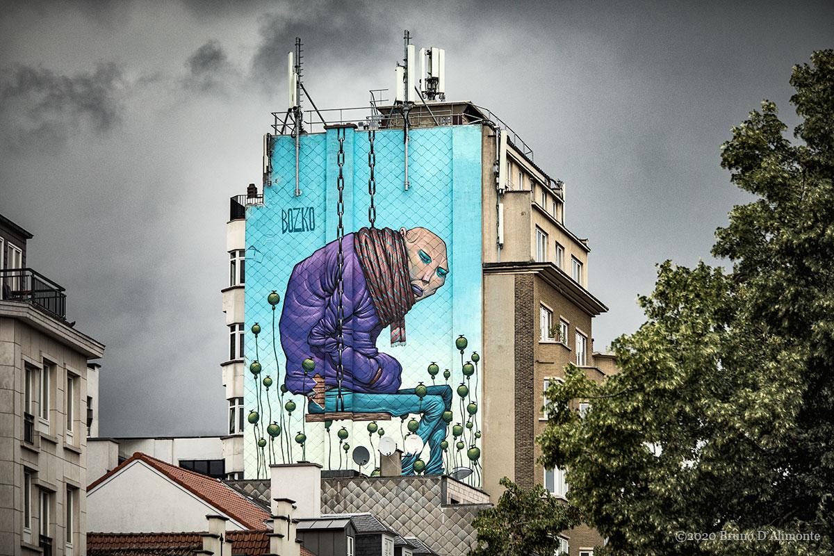 """Fresque du """"street artist"""" Bozko située à deux pas de la place Saint Catherine de Bruxelles. Elle représente un personnage au crane rasé assis sur une balançoire qui semble suspendu."""