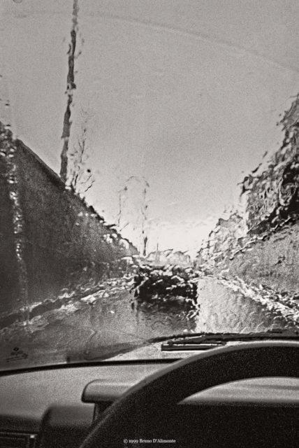 Photographie d'une voiture sous une pluie battante dont l'eau ruisselle depuis le pare-brise à la sortie Simonis de la petite ceinture de Bruxelles au niveau du tunnel Léopold II. © 1999 Bruno D'ALIMONTE