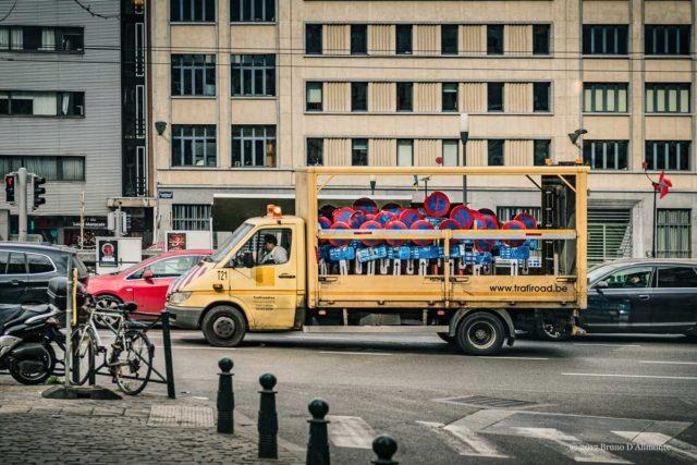 Véhicule de voirie transportant des panneaux d'interdiction de stationner en ville au milieu du trafic. Quai au charbonnage et boulevard de nieuport. Image issue de la collection Brussels'Eyes. © 2017 Bruno D'Alimonte