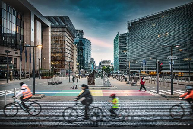 Place Shuman juin 2020, un passage piéton célèbre la cause LGBT tandis que des piétons et des vélos circulent. Illustration de Bruno D'ALIMONTE pour Brussels Eyes
