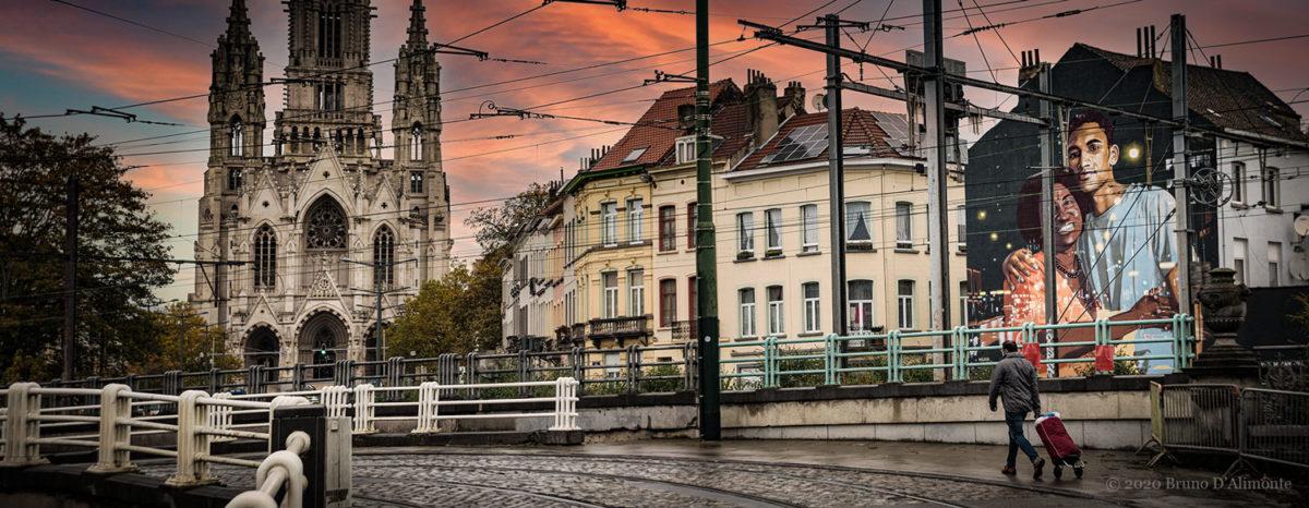 photographie panoramique représentant l'église Notre Dame de Laeken avec un passant muni d'un caddie et une fresque de street art de l'artiste NEAN dans un contexte pictural. Photo issue de la collection Brussels Eyes de Bruno D'Alimonte