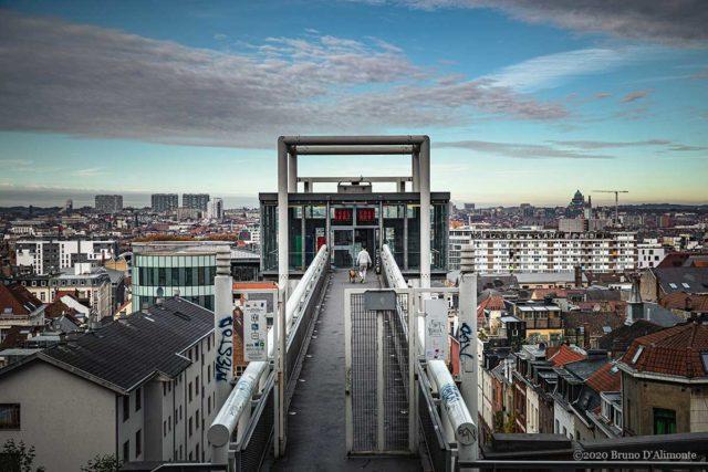 Vue panoramique de Bruxelles avec l'ascenseur des Marolles et un passant accompagné de son chien.