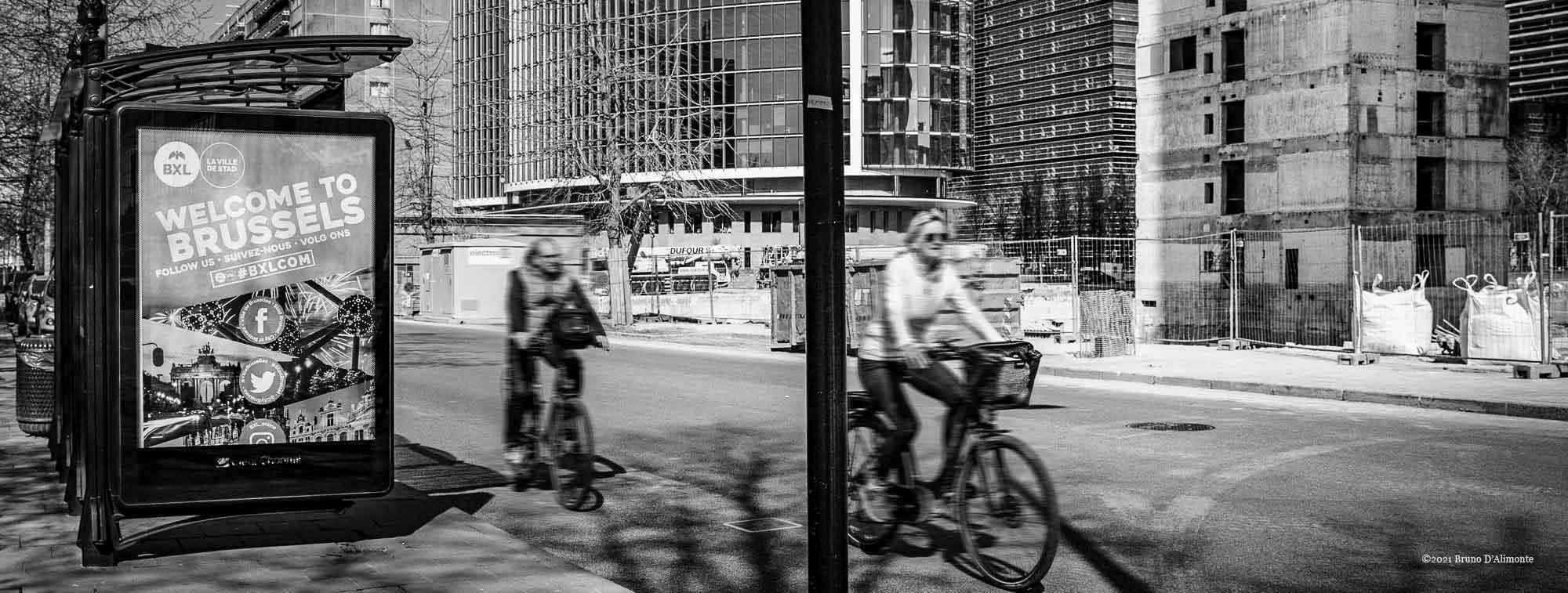 2 cyclistes de passage devant le projet Zin et les tours WTC alors qu'un panneau publicitaire nous invite à découvrir Bruxelles.